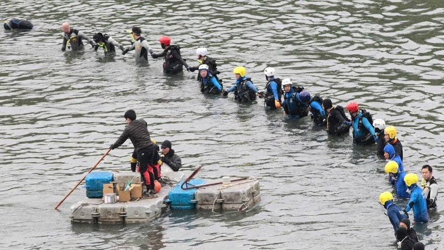 Search and rescue divers continue to search for missing persons at the site of a commercial plane crash in Taipei, Taiwan, Friday, Feb. 6, 2015. TransAsia Airways Flight 235, with 58 people aboard, clipped a bridge shortly after takeoff and crashed into a river in the island's capital of Taipei on Wednesday morning. (AP Photo/Wally Santana)