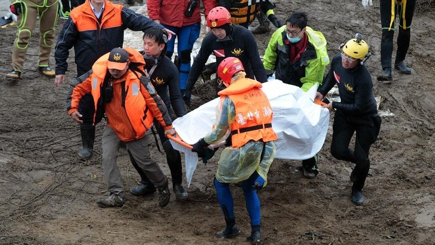 Search and rescue divers carry a recovered body at the site of a commercial plane crash in Taipei, Taiwan, Friday, Feb. 6, 2015. TransAsia Airways Flight 235 with 58 people aboard clipped a bridge shortly after takeoff and crashed into a river in the island's capital of Taipei on Wednesday morning. (AP Photo/Wally Santana)