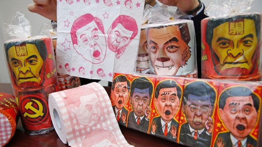 Rolls of toilet paper and packages of tissue paper printed with images of pro-Beijing Hong Kong Chief Executive Leung Chun-ying are shown by Hong Kong Democratic Party Vice Chairman Lo Kin-hei at his office in Hong Kong Saturday, Feb. 7, 2015. Lo said Saturday Chinese authorities seized about 8,000 rolls of the toilet paper and another 20,000 packages of the tissue paper, just ahead of Chinese New Year's when the rolls would have been sold. (AP Photo/Kin Cheung)