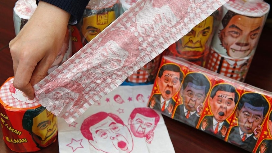 Hong Kong Democratic Party Vice Chairman Lo Kin-hei shows off rolls of toilet paper and packages of tissue paper printed with images of pro-Beijing Hong Kong Chief Executive Leung Chun-ying at his office in Hong Kong Saturday, Feb. 7, 2015. Lo said Saturday Chinese authorities seized about 8,000 rolls of the toilet paper and another 20,000 packages of the tissue paper, just ahead of Chinese New Year's when the rolls would have been sold. (AP Photo/Kin Cheung)