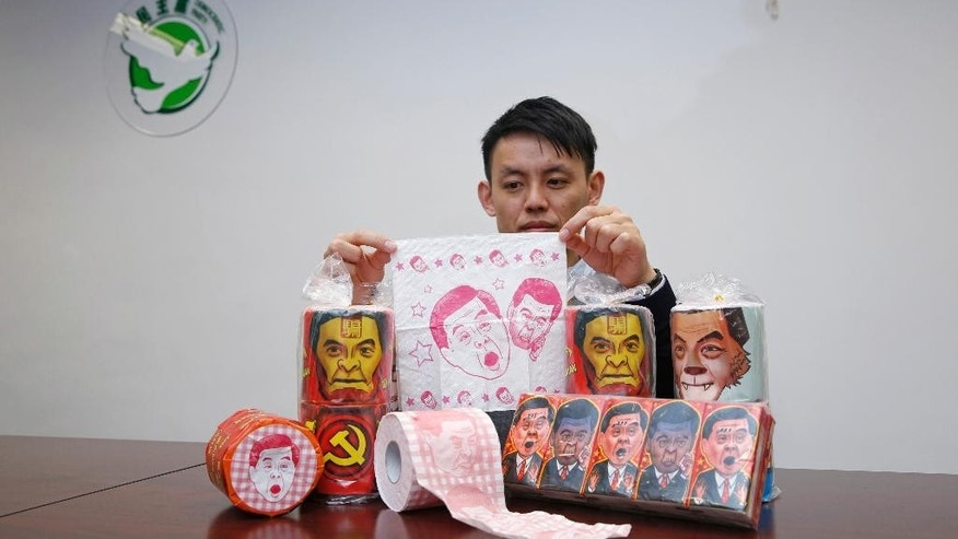 Hong Kong Democratic Party Vice Chairman Lo Kin-hei poses with rolls of toilet paper and packages of tissue paper printed with images of pro-Beijing Hong Kong Chief Executive Leung Chun-ying at his office in Hong Kong Saturday, Feb. 7, 2015. Lo said Saturday Chinese authorities seized about 8,000 rolls of the toilet paper and another 20,000 packages of the tissue paper, just ahead of Chinese New Year's when the rolls would have been sold. (AP Photo/Kin Cheung)