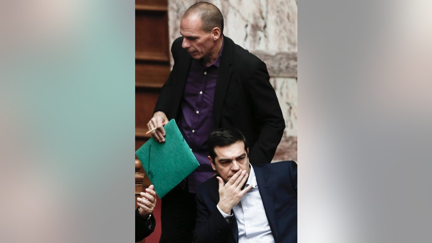 Greek Minister Alexis Tsipras, front, looks on as Finance Minister Yanis Varoufakis stands behind him during the vote for the president of Greece's parliament in Athens, on Friday, Feb. 6, 2015. Barely 10 days after radical left-wing Syriza was swept to power in Athens, analysts expect a compromise over Greece's debts to emerge, allowing it to remain a member of the 19-country eurozone. The finance ministers of the 19-country eurozone are to meet at a special meeting Wednesday on the eve of a summit of European Union leaders to discuss Greece's debts. (AP Photo/Petros Giannakouris )
