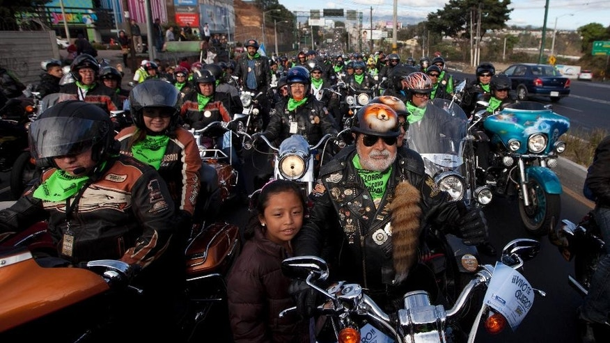 Eddie Villadelon, right, leader and organizer of the annual motorcycle pilgrimage to the church of the Black Christ of Esquipulas, leads the pilgrims as they leave Guatemala City, Saturday, Feb. 7, 2015. Pilgrims from all over Central America annually flock the city of Esquipulas to pay homage to a Black Christ located there. (AP Photo/Moises Castillo)
