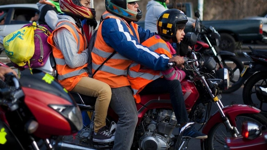 A biker and his family leave Guatemala City during a pilgrimage to the church of the Black Christ of Esquipulas, Saturday, Feb. 7, 2015. Pilgrims from all over Central America annually flock the city of Esquipulas to pay homage to a Black Christ located there. (AP Photo/Moises Castillo)