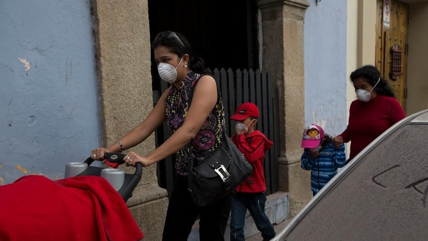 A family covers their faces with surgical masks as they walk next to a car covered with ash from the eruption of the Fuego Volcano at Antigua Guatemala, Saturday, Feb. 7, 2015. A national disaster preparedness official in Guatemala said that the Fire Volcano has erupted, spewing incandescent rock and ash that dusted surrounding communities. (AP Photo/Moises Castillo)