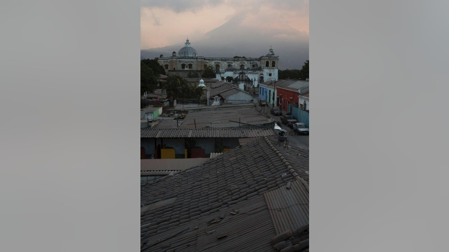 Rooftops and San Francisco church, background, are covered with ash from the eruption of the Fuego Volcano at Antigua Guatemala, Saturday, Feb. 7, 2015. A national disaster preparedness official in Guatemala said that the Fire Volcano has erupted, spewing incandescent rock and ash that dusted surrounding communities.  (AP Photo/Moises Castillo)