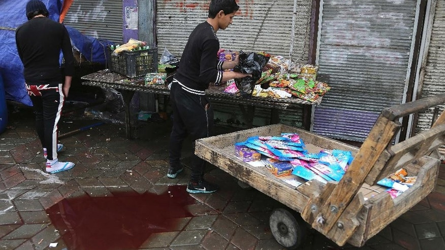 Iraqi shop owners clean up the site of a suicide bombing that targeted a street filled with hardware stores, killing over 20 people and wounding at least 45, in the Iraqi capital's southeastern neighborhood of New Baghdad, Saturday, Feb. 7, 2015. A pair of bombings in the Iraqi capital Saturday killed more than three dozen people hours before the city's longtime curfew was set to come to an end. The other attack was in central Baghdad's popular Shorja market where police said two improvised explosive devices detonated 25 meters apart from one another. (AP Photo/Karim Kadim)