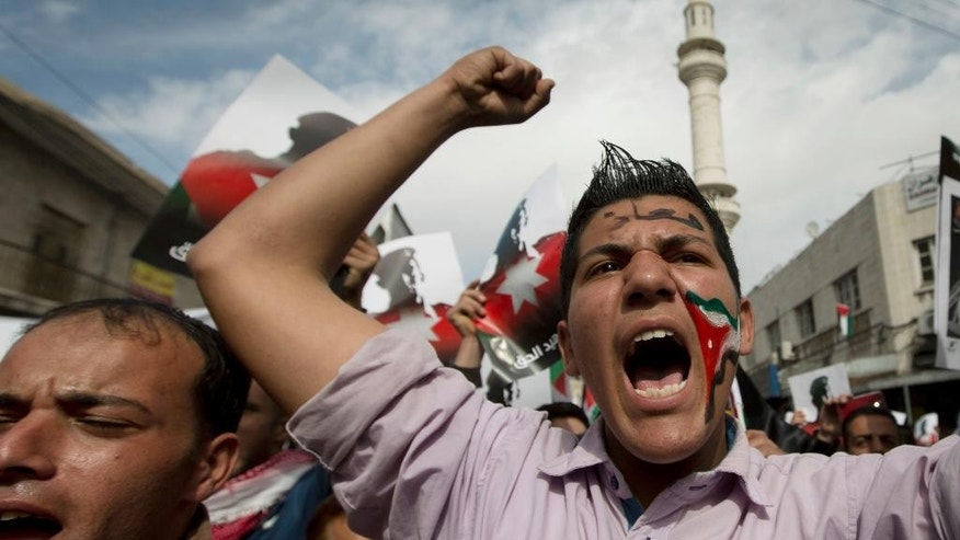 "Demonstrators, one with a Jordanian flag image painted on his face and Arabic that reads, ""Muath,"" as in slain Jordanian pilot, Lt. Muath al-Kaseasbeh, chant anti-Islamic State group slogans during a rally in Amman, Jordan, Friday, Feb. 6, 2015. Several thousand people marched after Muslim Friday prayers in support of King Abdullah II's pledge of a tough military response to the killing of the pilot. (AP Photo/Nasser Nasser)"