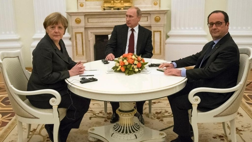 Russian President Vladimir Putin, center, French President Francois Hollande, right, and German Chancellor Angela Merkel pose for a photo during their meeting in the Kremlin in Moscow, Russia, Friday, Feb. 6, 2015. Talks among the leaders of Russia, France and Germany on a peace initiative for Ukraine ended early Saturday with an announcement that Russian President Vladimir Putin and his Ukrainian counterpart would discuss a proposal to end the fighting in a four-way telephone call this weekend.(AP Photo/Alexander Zemlianichenko)