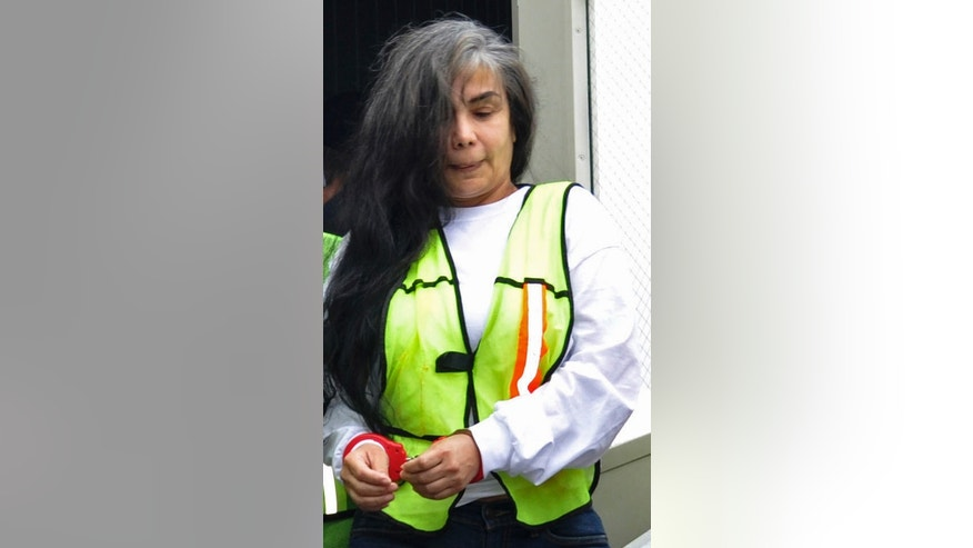 "FILE - In this Aug. 20, 2013, file photo, provided by Mexico's Interior Department shows Sandra Avila Beltran in handcuffs as she is escorted by federal authorities upon arrival to Benito Juarez airport in Mexico City. A Mexican federal judge has thrown out a five-year, money-laundering sentence against Avila, ordering the immediate release of the so-called ""Queen of the Pacific"" for her alleged role as a liaison between Mexican and Colombian cartels. A statement issued Saturday Feb. 7, 2015, by the Attorney General's Office says the judge ruled that Avila had already been tried for the same crime in Mexico and the United States. (AP Photo/Mexico Interior Department, File)"