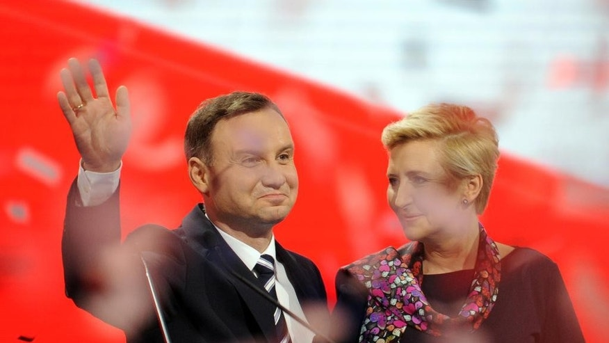 Candidate of Poland's main conservative opposition party Law and Justice in the May presidential elections, Andrzej Duda with wife Agata greet supporters during a festive opening of his campaign, as confetti fly,  in Warsaw, Poland, Saturday, Feb. 7, 2015. (AP Photo/Alik Keplicz)