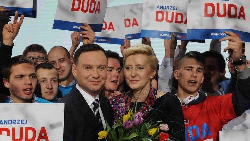 Candidate of Poland's main conservative opposition party Law and Justice in the May presidential elections, Andrzej Duda with wife Agata are surrounded by supporters during a festive opening of his campaign, as confetti flies in the air,  in Warsaw, Poland, Saturday, Feb. 7, 2015. (AP Photo/Alik Keplicz)