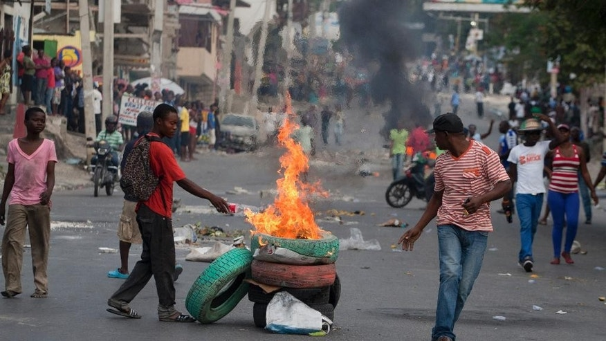 Demonstrators burn tires in the street during an anti-government march in Port-au-Prince, Haiti, Saturday, Feb. 7, 2015. Several thousand protesters marched through Haiti's capital to demand lower gas prices and the ouster of President Michel Martelly. ( AP Photo/Dieu Nalio Chery)