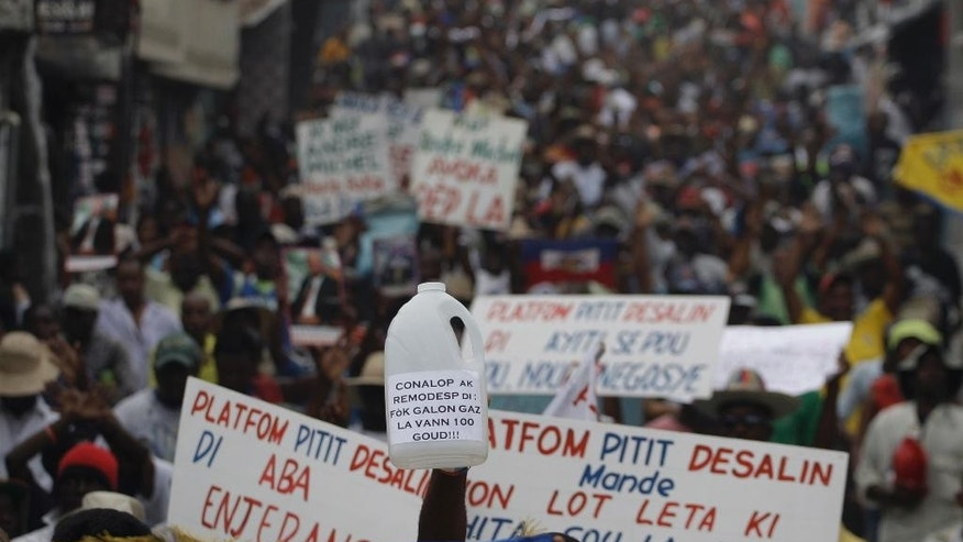 Demonstrators hold up signs with anti-government slogans during a protest in Port-au-Prince, Haiti, Saturday, Feb. 7, 2015. Several thousand protesters marched through Haiti's capital to demand lower gas prices and the ouster of President Michel Martelly. ( AP Photo/Dieu Nalio Chery)