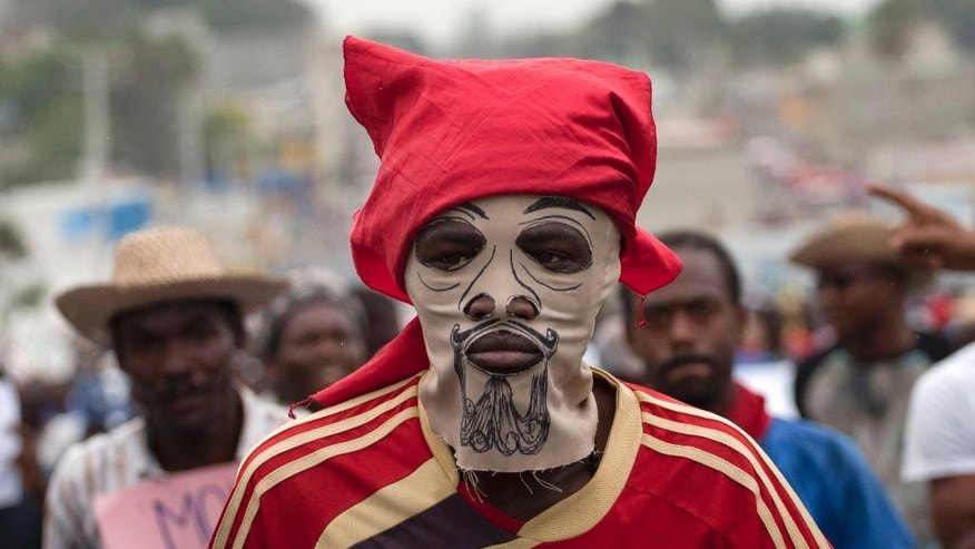 A masked demonstrator attends an anti-government protest in Port-au-Prince, Haiti, Saturday, Feb. 7, 2015. Several thousand protesters marched through Haiti's capital to demand lower gas prices and the ouster of President Michel Martelly. ( AP Photo/Dieu Nalio Chery)