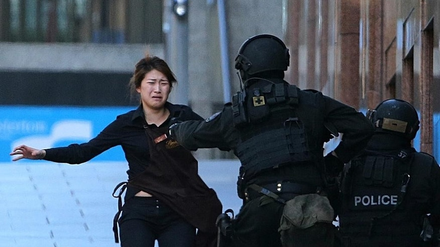 Dec. 15, 2014: In this file photo, Bae Jie-un, a staff member of a Sydney cafe and one of the hostages, runs to armed tactical response police officers for safety after she escaped from a cafe under siege in Sydney, Australia. (AP)
