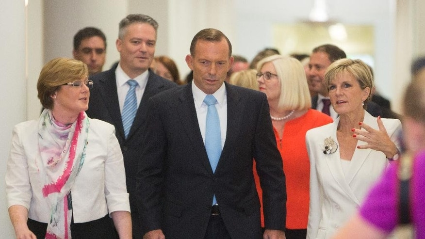 Australian Prime Minister Tony Abbott, center, surrounded by supporters, walks to a meeting to face a potential leadership challenge Monday, Feb. 9, 2015.   Beleaguered Prime Minister Abbott survived an internal government challenge to his leadership on Monday, despite a revolt by dozens of colleagues that leaves him politically damaged.(AP Photo/Andrew Taylor)