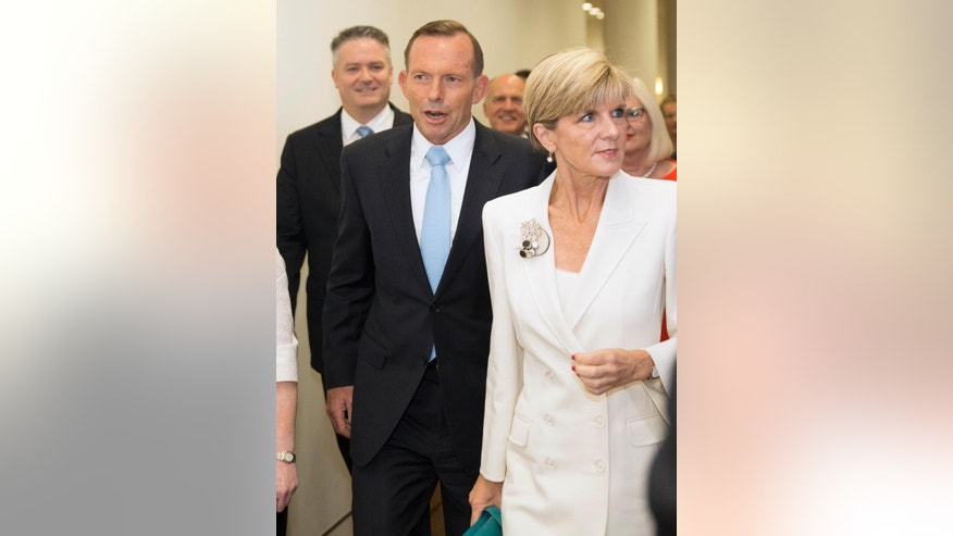 Australian Prime Minister Tony Abbott, center, surrounded by supporters, walks to a meeting to face a potential leadership challenge Monday, Feb. 9, 2015.  Australia's beleaguered Prime Minister  Abbott survived an internal government challenge to his leadership on Monday, despite a revolt by dozens of colleagues that leaves him politically damaged.(AP Photo/Andrew Taylor)