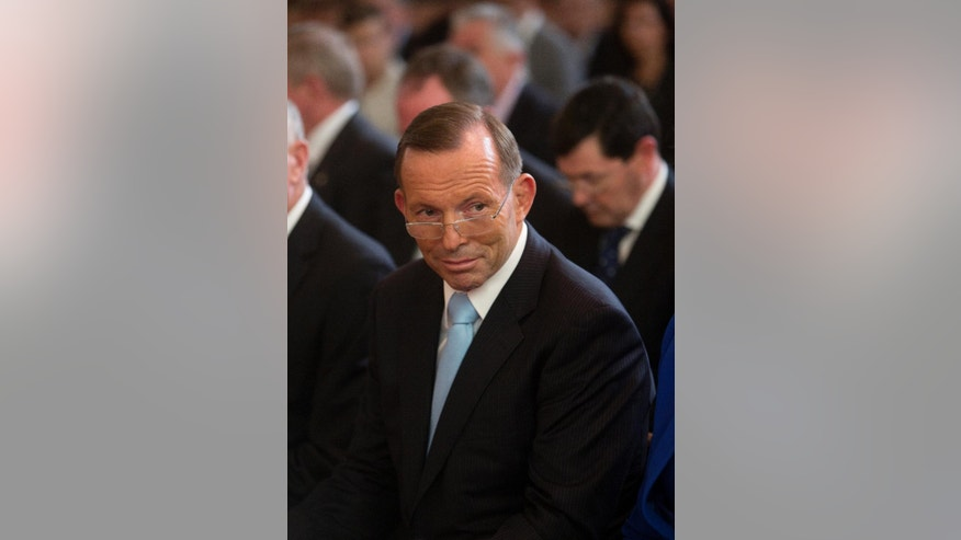 Australian Prime Minister Tony Abbott attends an Ecumenical  church service, ahead of the start of this parliamentary session Monday, Feb. 9, 2015.   Beleaguered Prime Minister Abbott survived an internal government challenge to his leadership on Monday, despite a revolt by dozens of colleagues that leaves him politically damaged.(AP Photo/Andrew Taylor)