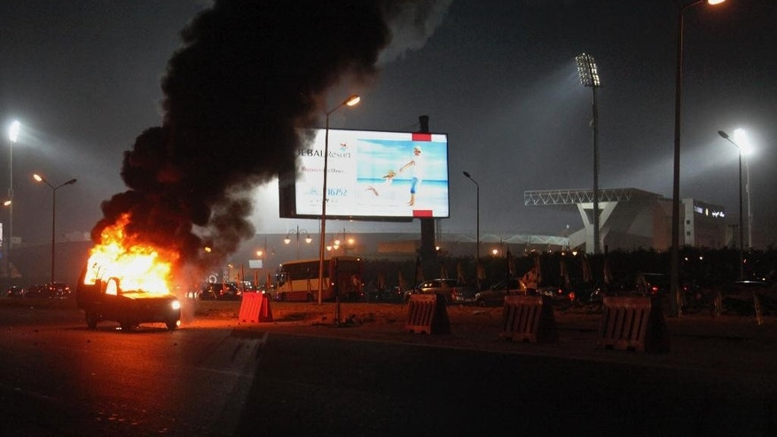 A pickup truck bursts into flames as a riot breaks out outside of a soccer match between Egyptian Premier League clubs Zamalek and ENPPI at Air Defense Stadium in a suburb east of Cairo, Egypt, Sunday, Feb. 8, 2015. The riot broke out Sunday night outside of the major soccer game, with a stampede and fighting between police and fans killing at least 22 people, authorities said. (AP Photo/Ahmed Abd El-Gwad, El Shorouk newspaper) EGYPT OUT