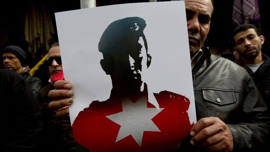 "A Jordanian demonstrator carries a poster with a picture of slain Jordanian pilot, Lt. Muath al-Kaseasbeh, and Arabic that reads, ""Muath is the martyr of the right,"" during an anti-IS group rally in Amman, Jordan, Friday, Feb. 6, 2015. Several thousand people marched after Muslim Friday prayers in support of the king's pledge of a tough military response to the killing of the pilot. (AP Photo/Nasser Nasser)"
