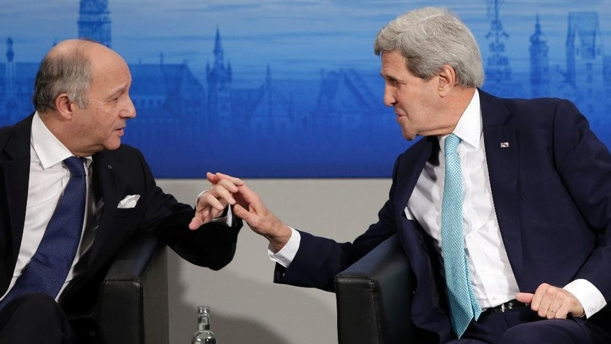 French Foreign Minister Laurent Fabius, left, chats with U.S. Secretary of State John Kerry  on the podium during the 51. Security Conference in Munich, Germany, Sunday, Feb. 8, 2015.  (AP Photo/Matthias Schrader)