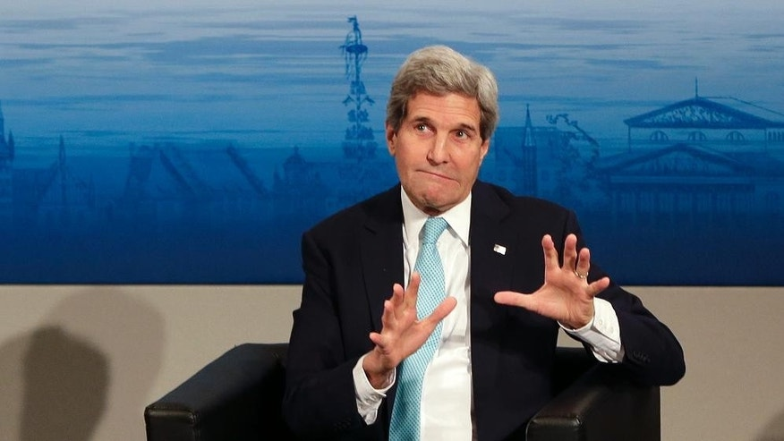 U.S. Secretary of State John Kerry gestures as he takes place on the podium during the 51. Security Conference in Munich, Germany, Sunday, Feb. 8, 2015.  (AP Photo/Matthias Schrader)