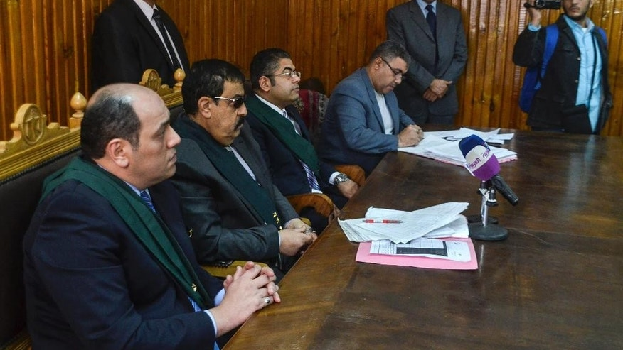 In this Wednesday, Feb. 4, 2015 photo, Egyptian Judge Mohammed Nagi Shehata, third left, presides over a court hearing in a case against 230 people including Ahmed Douma, one of the leading activists behind the country's 2011 uprising, in a courtroom of Torah prison, Cairo, Egypt. If you're branded an enemy of the state in Egypt, you may never get the chance to defend yourself in a justice system racking up convictions in lop-sided mass trials according to legal observers and human rights groups. President Abdel-Fattah el-Sissi is unrepentant, arguing his government must enforce stability at the expense of human rights in a country where many thousands face prosecution after years of unrest. (AP Photo/Mohammed El-Raaei)