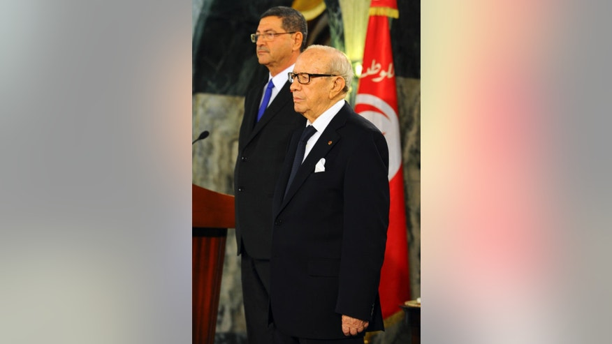 "Tunisian President Beji Caid Essebsi, front and new Prime Minister Habib Essid stand at attention during a cabinet takeover ceremony in Tunis, Friday, Feb. 6, 2015.  Prime Minister Essid, whose cabinet has ministers from four parties including the powerful Islamist group, promised ""work and nothing but work"" on the country's economic and security problems.  (AP Photo/Hassene Dridi)"