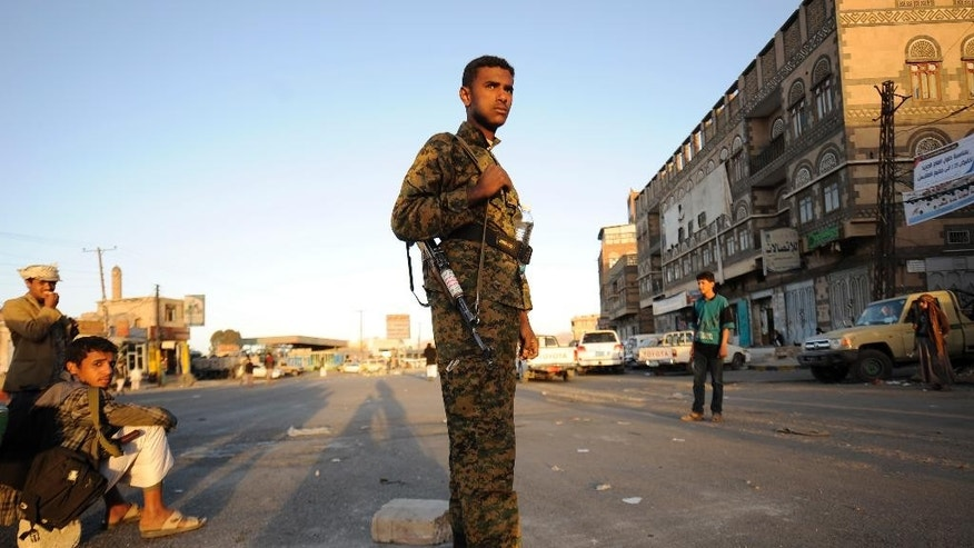"""A Houthi Shiite fighter wearing an army uniform, stands guard outside of a sports stadium during a rally in Sanaa, Yemen, Saturday, Feb. 7, 2015. A day after taking power, Shiite rebels in Yemen found themselves increasingly under pressure Saturday as thousands protested against their rule and a group of nearby countries denounced their """"coup."""" (AP Photo/Hani Mohammed)"""