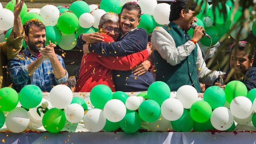 "Aam Aadmi Party, or Common Man's Party, leaders Arvind Kejriwal, center, and Ashutosh, second left, hug as they celebrate news of their party's performance in New Delhi, India, Tuesday, Feb. 10, 2015. The upstart anti-corruption party appeared set  to install a state government in India's capital in a huge blow for Prime Minister Narendra Modi's Hindu nationalist party. As early trends pointed to an overwhelming win for the AAP, the party's jubilant supporters began cheering and dancing in celebration, yelling ""Five Years Kejriwal."" (AP Photo/Manish Swarup)"