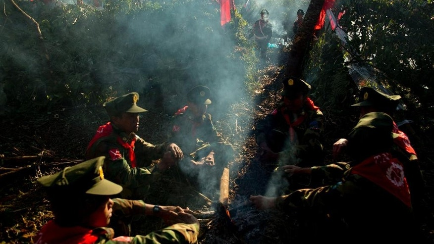 In this Jan. 12, 2015 photo, officers with the Ta'ang National Liberation Army gather in the steep hillside jungles in Mar Wong, a village in northern Shan state, Myanmar. The tiny ethnic armed group, fighting for the rights of a half-million Buddhist minority Ta'ang, was marking the anniversary of it's insurrection 52 years ago against the rule of then-dictator Gen. Ne Win. As President Thein Sein struggles to reach a nationwide peace agreement before his term ends later this year, the TNLA has turned out to be one of his most intractable thorns, refusing to sign a ceasefire agreement. (AP Photo/Gemunu Amarasinghe)