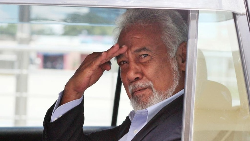 Former East Timorese guerrilla leader Xanana Gusmao salutes at the media as he leaves after a meeting with President Taur Matan Ruak in Dili, East Timor, Monday, Feb. 9, 2015. The president on Monday accepted the resignation of the country's independence hero as prime minister ahead of an expected restructuring of the government. (AP Photo/Kandhi Barnez)
