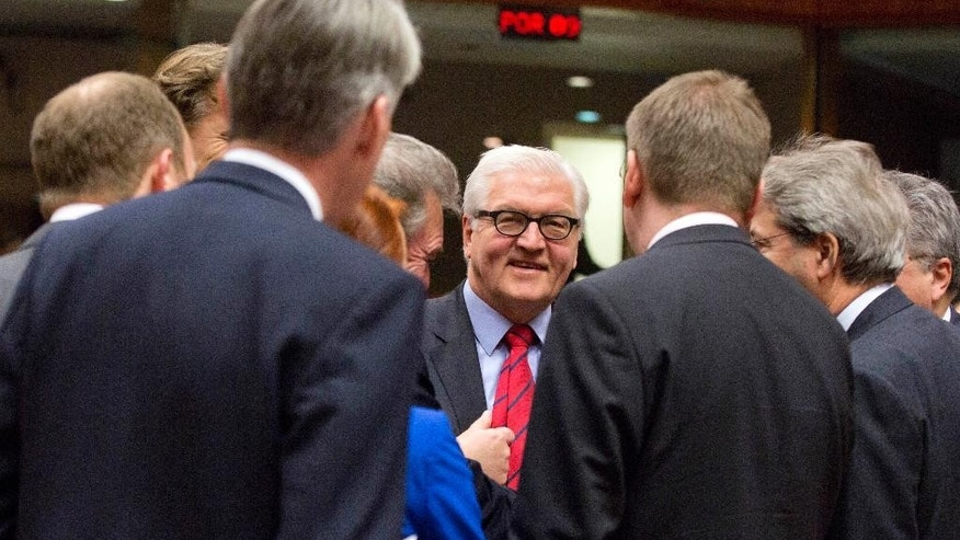 German Foreign Minister Frank-Walter Steinmeier, center, speaks with a group of European foreign ministers during a meeting of EU foreign ministers at the EU Council building in Brussels on Monday, Feb. 9, 2015. European Union foreign ministers have thrown their weight behind fresh diplomatic efforts to end the conflict in Ukraine as they assess whether to expand the EU sanctions list targeting separatists and Russian nationals. (AP Photo/Virginia Mayo)