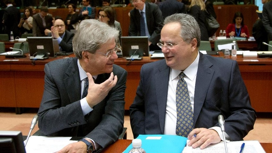 Italian Foreign Minister Paolo Gentiloni, left, speaks withGreek Foreign Minister Nikos Kotzias during a meeting of EU foreign ministers at the EU Council building in Brussels on Monday, Feb. 9, 2015. European Union foreign ministers have thrown their weight behind fresh diplomatic efforts to end the conflict in Ukraine as they assess whether to expand the EU sanctions list targeting separatists and Russian nationals. (AP Photo/Virginia Mayo)