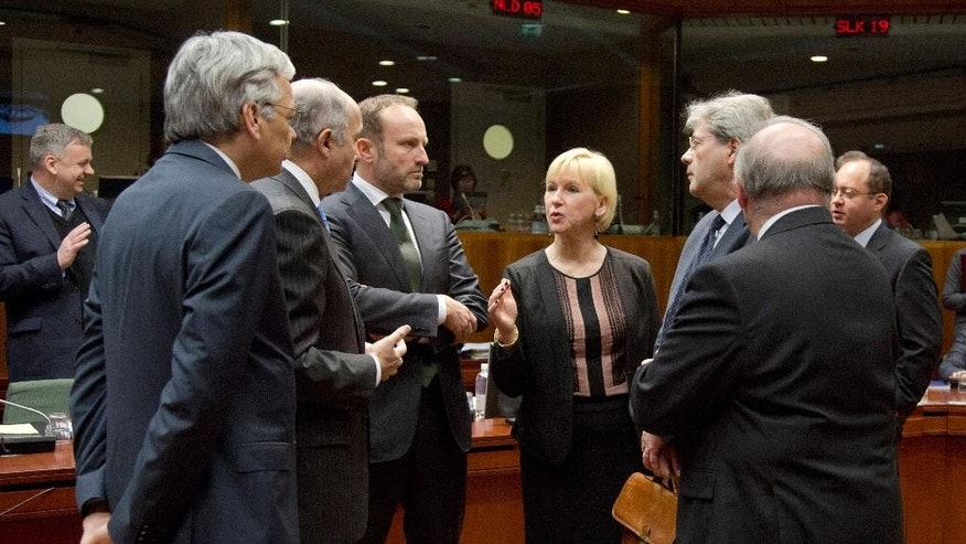 Swedish Foreign Minister Margot Wallstrom, center, speaks with, from left, Belgian Foreign Minister Didier Reynders, French Foreign Minister Laurent Fabius, Danish Foreign Minister Martin Lidegaard, Italian Foreign Minister Paolo Gentiloni, Romanian Foreign Minister Bogdan Aurescu and Malta's Foreign Minister George Vella during a meeting of EU foreign ministers at the EU Council building in Brussels on Monday, Feb. 9, 2015. European Union foreign ministers have thrown their weight behind fresh diplomatic efforts to end the conflict in Ukraine as they assess whether to expand the EU sanctions list targeting separatists and Russian nationals. (AP Photo/Virginia Mayo)