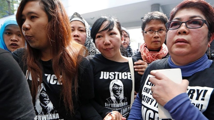 Indonesian maid Erwiana Sulistyaningsih, center, accompanied by her supporters, walks out from a court in Hong Kong, Tuesday, Feb. 10, 2015. A Hong Kong woman who was accused of torturing her Indonesian maid in a case that sparked outrage for the scale of its brutality was convicted of a slew of assault and other charges on Tuesday. A judge found Law Wan-tung guilty of 18 charges that also included criminal intimidation and failure to pay wages or give time off work to Sulistyaningsih. (AP Photo/Kin Cheung)