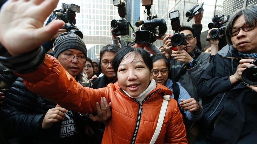 Indonesian maid Erwiana Sulistyaningsih, center, waves to her supporters as she arrives at a court in Hong Kong, Tuesday, Feb. 10, 2015. A Hong Kong woman who was accused of torturing her Indonesian maid in a case that sparked outrage for the scale of its brutality was convicted of a slew of assault and other charges on Tuesday. A judge found Law Wan-tung guilty of 18 charges that also included criminal intimidation and failure to pay wages or give time off work to Sulistyaningsih. (AP Photo/Kin Cheung)