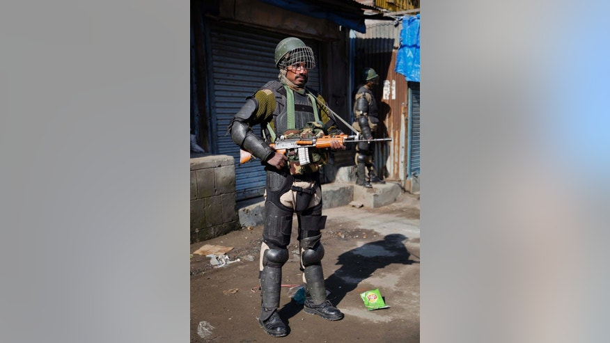 An Indian paramilitary soldier stands guard during a strike in Srinagar, India, Monday, Feb. 9, 2015. Hundreds of armed police and paramilitary soldiers are patrolling the disputed region of Kashmir where anti-India separatists called a strike to protest the secret execution two years ago of a former Kashmiri rebel and medical student Mohammed Afzal Guru. Many in this mostly Muslim region believe Guru was not given a fair trial on charges of involvement in 2001 Parliament attack that killed 14 people, including five gunmen. (AP Photo/Mukhtar Khan)