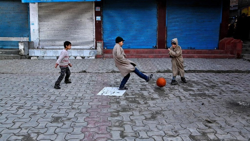 Kashmiri children play soccer at a closed market during a strike in Srinagar, India, Monday, Feb. 9, 2015. Hundreds of armed police and paramilitary soldiers are patrolling the disputed region of Kashmir where anti-India separatists called a strike to protest the secret execution two years ago of a former Kashmiri rebel and medical student Mohammed Afzal Guru. Many in this mostly Muslim region believe Guru was not given a fair trial on charges of involvement in 2001 Parliament attack that killed 14 people, including five gunmen. (AP Photo/Mukhtar Khan)
