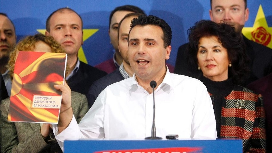 "Zoran Zaev, the leader of the opposition Social-Democratic Alliance of Macedonia, shows a file named: ""Freedom and Democracy for Macedonia"", during a news conference in the party headquarters in Skopje,  Macedonia, Monday, Feb. 9, 2015.  Zaev has accused the conservative government of carrying out illegal wiretaps on more than 20,000 people, including his own, and accused conservative Prime Minister Nikola Gruevski of heading the alleged surveillance operation. (AP Photo/Boris Grdanoski)"