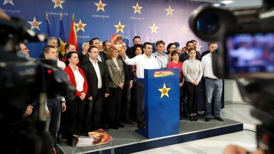 Zoran Zaev, center, the leader of the opposition Social-Democratic Alliance of Macedonia, speaks from the podium during a news conference in the party headquarters in Skopje, Macedonia, Monday, Feb. 9, 2015.  Zaev has accused the conservative government of carrying out illegal wiretaps on more than 20,000 people, including his own, and accused conservative Prime Minister Nikola Gruevski of heading the alleged surveillance operation. (AP Photo/Boris Grdanoski)