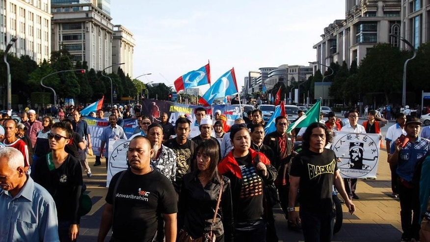 Supporters of Malaysian opposition leader Anwar Ibrahim march towards the Palace of Justice at Putrajaya, Malaysia, Tuesday, Feb. 10, 2015. Malaysia's top court has rejected a final appeal from Anwar and sent him back to jail in a case seen at home and aboard as politically motivated to eliminate any threats to the government. (AP Photo/Joshua Paul)