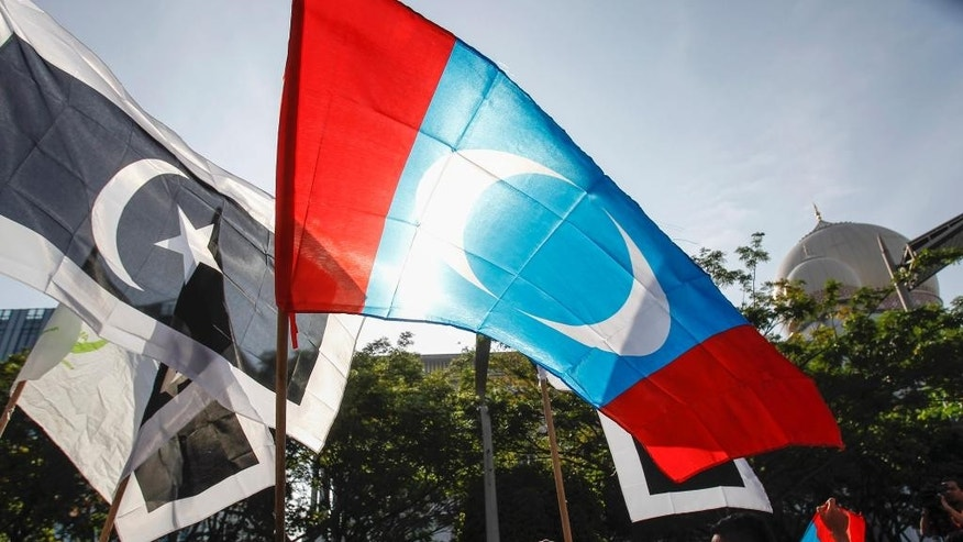 Supporters of Malaysian opposition leader Anwar Ibrahim waves People's Justice Party flag, center, in front of the Palace of Justice at Putrajaya, Malaysia, Tuesday, Feb. 10, 2015. Malaysia's top court has rejected a final appeal from Anwar and sent him back to jail in a case seen at home and aboard as politically motivated to eliminate any threats to the government. (AP Photo/Joshua Paul)