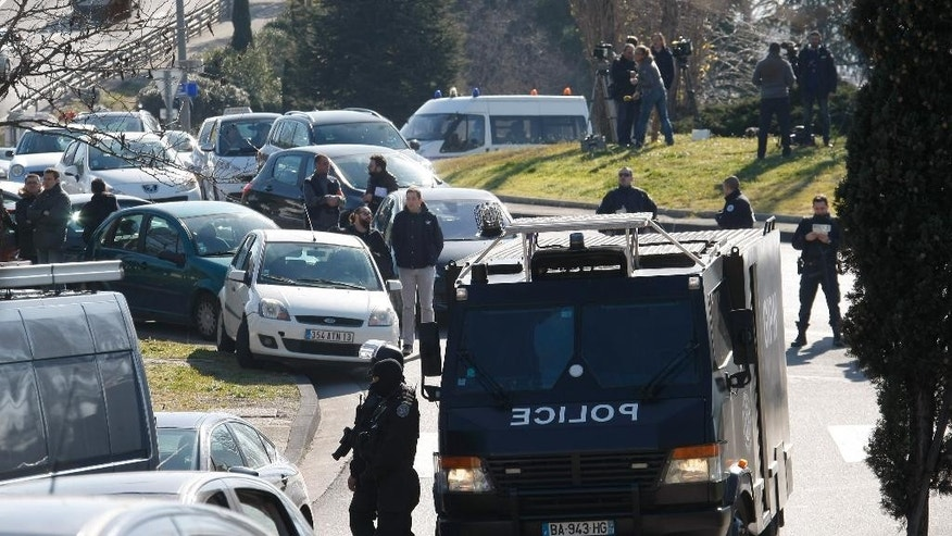 Police officers block the entrance of the Castellane housing project of Marseille, southern France, Monday, Feb.9, 2015. Police say gunmen have fired automatic weapons at the edge of a housing project the same day as the prime minister planned to visit the city. The project is rife with drug gangs and violence. No injuries were immediately reported. (AP Photo/Claude Paris)