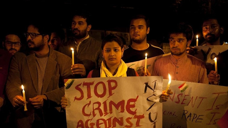 Indian youth hold candles during a protest against sexual violence in New Delhi, India, Monday, Feb. 9, 2015.Police were searching Monday for a man who raped a Japanese student sightseeing in northern India, while elsewhere they announced the arrest of eight men suspected of brutally raping and killing a Nepalese woman, as India authorities continue to struggle to address chronic sexual violence. (AP Photo/ Tsering Topgyal)
