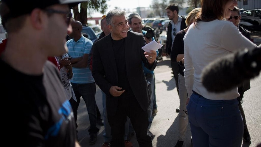 In this photo taken on Monday, Feb. 2, 2015, Yair Lapid, Israeli former finance minister and leader of Yesh Atid party, smiles after delivering a statement outside a prison in Ramle, central Israel. Lapid's party came from nowhere in the 2013 election to capture 19 of the Knesset's 120 seats, second only to Prime Minister Benjamin Netanyahu. But instead of leading his largely secular and middle-class supporters into opposition to battle Netanyahu, he cut a Faustian bargain with his right-wing rival and kept him in power, wilting his own grass roots in the process. (AP Photo/Ariel Schalit)