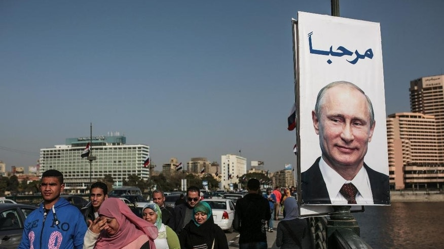 "People walk past a banner with a picture of Russian President Vladimir Putin with Arabic that reads, ""welcome,"" along a bridge in Cairo, Egypt, Monday, Feb. 9, 2015. The Russian president is due to visit for two days on his first visit in a decade in a bid to expand influence. (AP Photo/Mosa'ab Elshamy)"