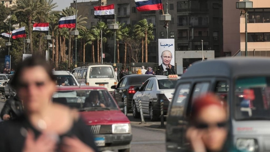 "People walk past a banner with a picture of Russian President Vladimir Putin that reads, ""welcome,"" along a bridge in Cairo, Egypt, Monday, Feb. 9, 2015. The Russian president is due to visit for two days on his first visit in a decade in a bid to expand influence. (AP Photo/Mosa'ab Elshamy)"