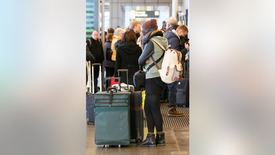 "Passengers wait  at the airport in Hamburg, northern Germany, Monday Feb. 9, 2015. Police have closed entrances to the airport in the German city of Hamburg, amid chaos caused by a security strike. Security personnel are staging strikes Monday at airports in Hamburg, Hannover and Stuttgart to press their demands for higher wages. German news agency dpa quoted Hamburg airport spokeswoman Stefanie Harder describing the situation at the airport as ""catastrophic."" About a quarter of all flights there have been canceled. (AP Photo/dpa, Bodo Marks)"